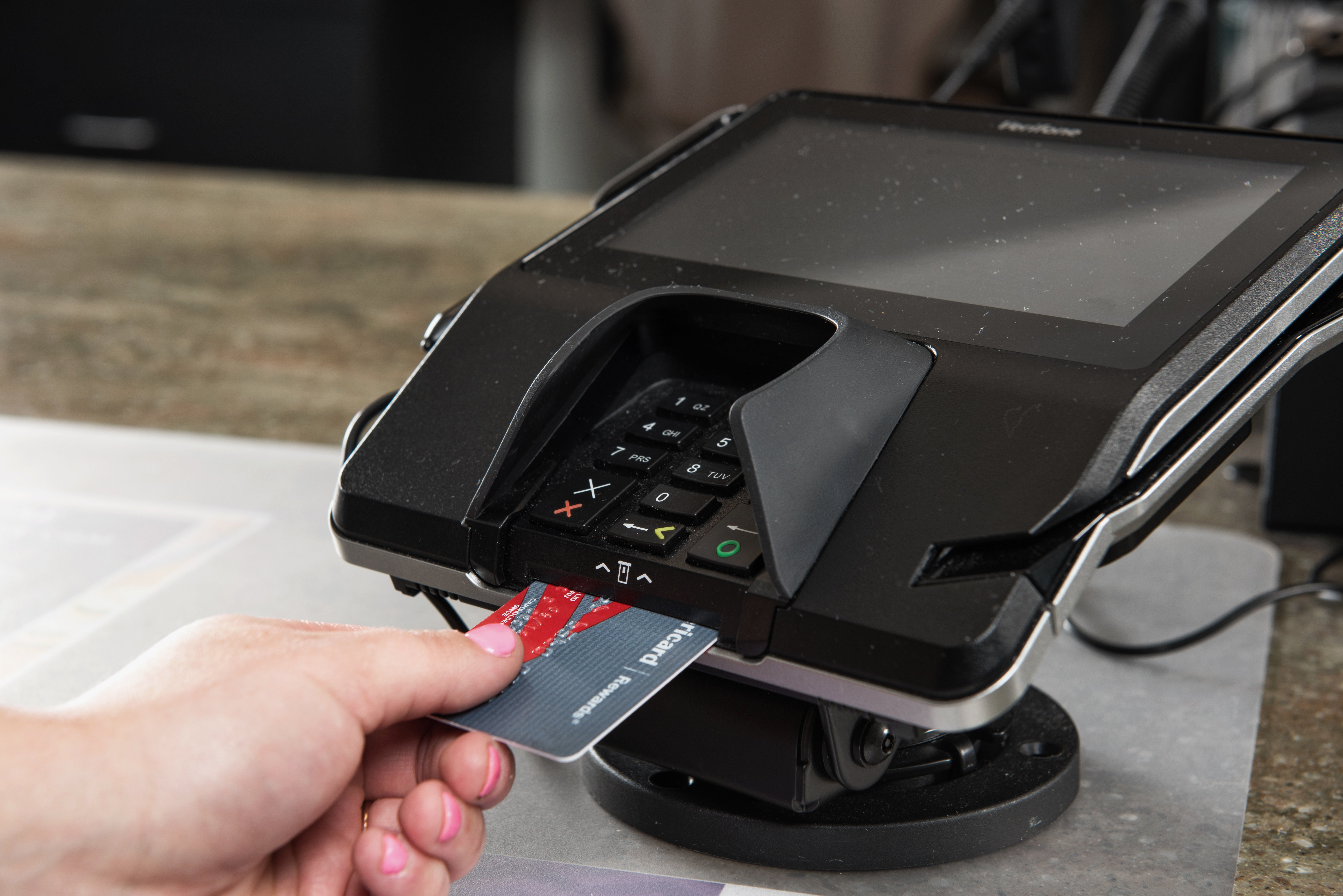 Pharmacy patient using their EMV card in an EMV terminal for secure credit card processing.