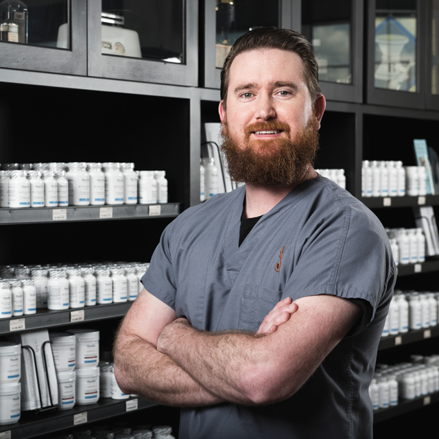 Pharmacy owner posing in his specialty and compounding pharmacy.
